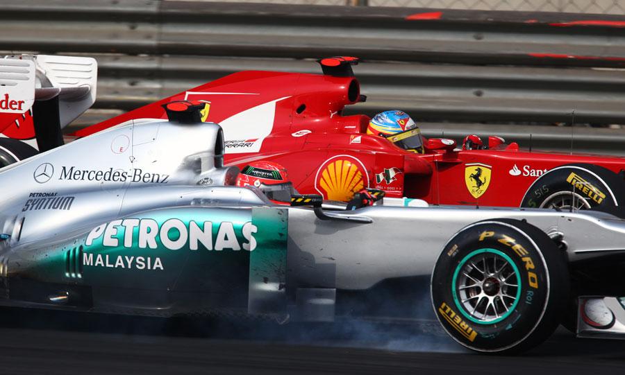 Michael Schumacher locks a wheel as he defends from Fernando Alonso