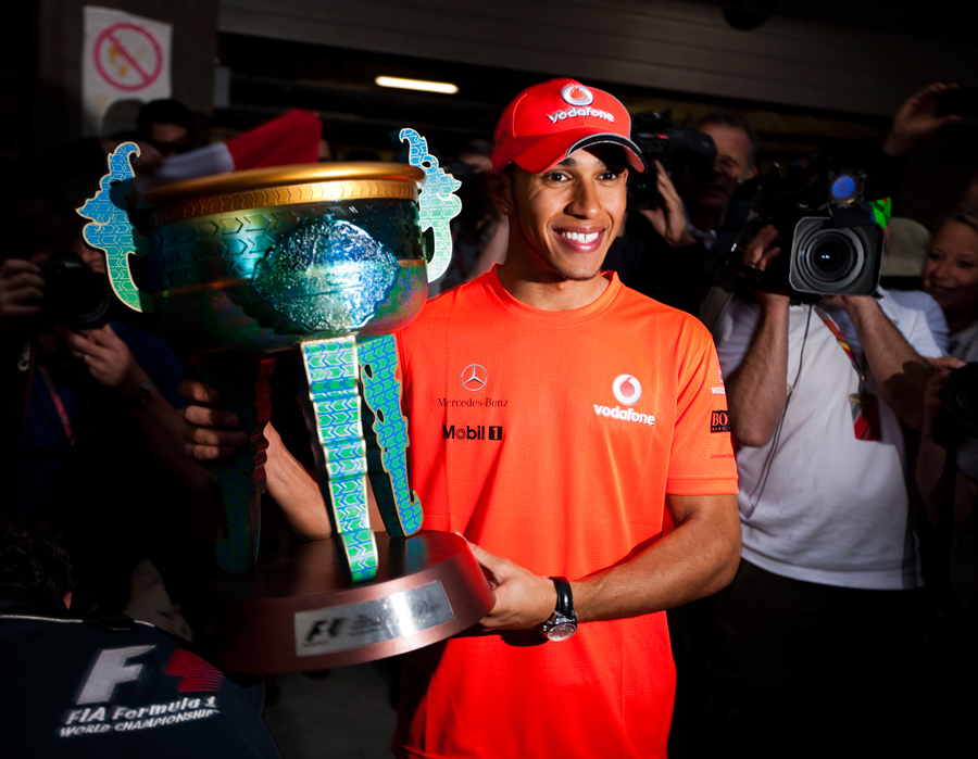 Lewis Hamilton poses with the trophy