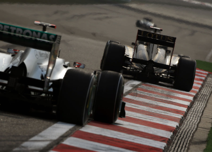 Nick Heidfeld holds off the Mercedes of Michael Schumacher through the final corner