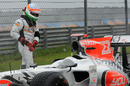 Narain Karthikeyan waits for a lift after stopping his HRT out on track early in the morning session