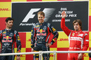 Fernando Alonso waves to the crowd on the podium alongside Mark Webber and Sebastian Vettel