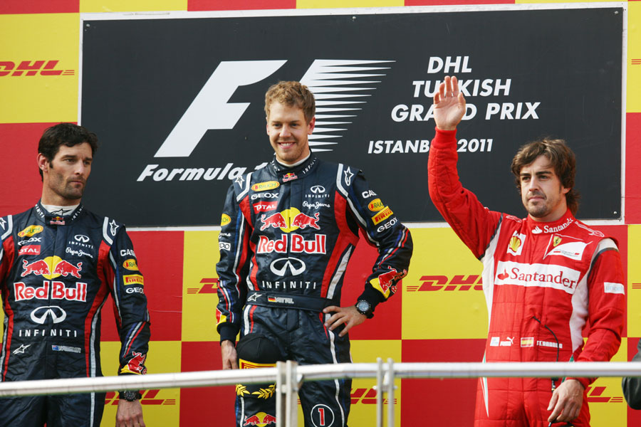 Fernando Alonso waves to the crowd on the podium alongside Mark Webber and Sebastian Vettel