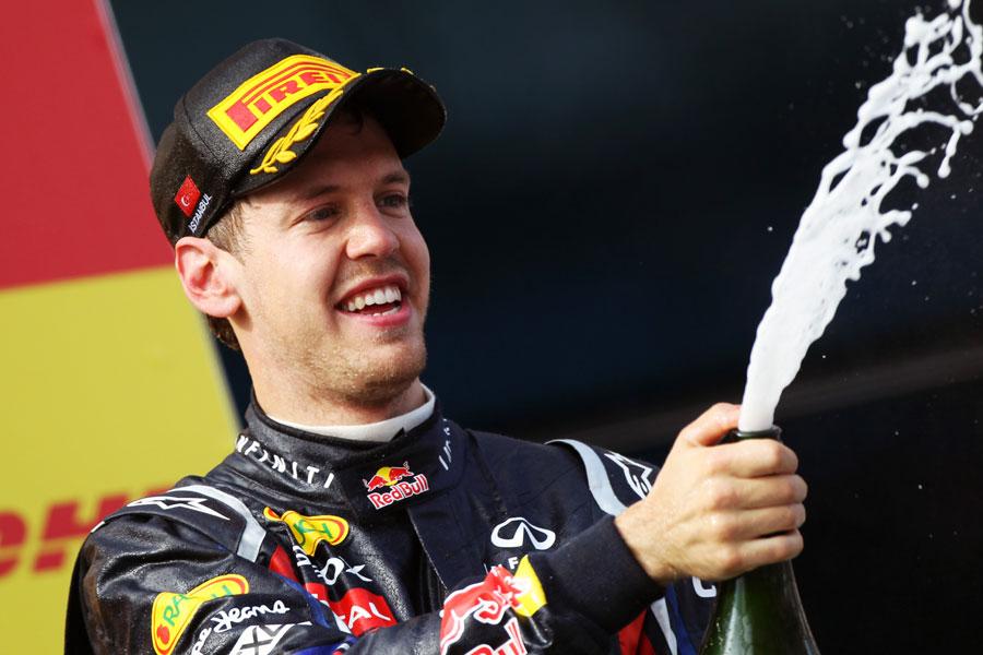 Sebastian Vettel sprays champagne on the podium