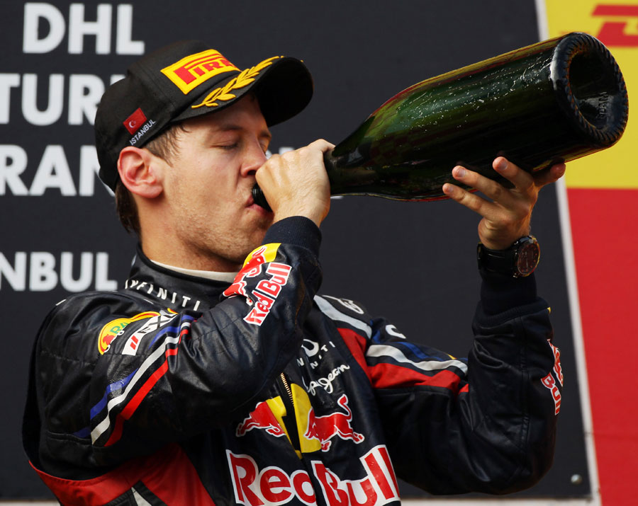 Sebastian Vettel takes a swig of champagne on the podium