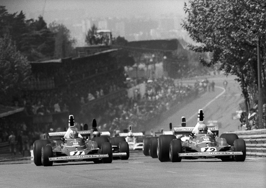 The Ferraris of Clay Regazzoni and Niki Lauda lead the pack away from the grid at the start of the race