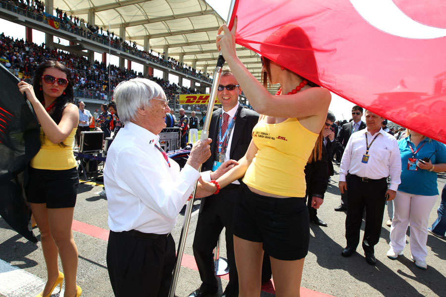 Bernie Ecclestone takes the Turkish falg off a grid girl for the start of the national anthem