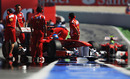 Fernando Alonso is wheeled back into his garage as Felipe Massa comes down the pit lane